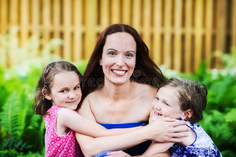 Döttrar som kramar deras moder royaltyfri bild
