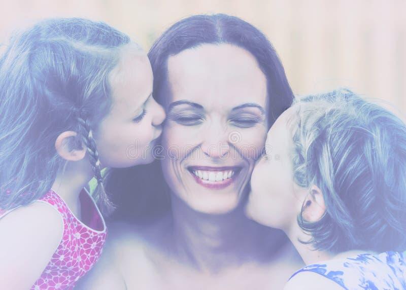Döttrar som kysser deras Retro moder - royaltyfria bilder
