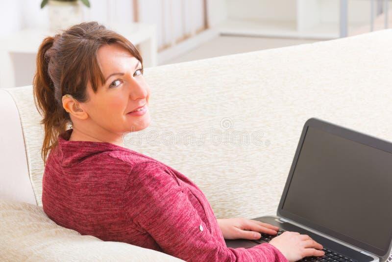 Döv kvinna som hemma använder bärbara datorn royaltyfria foton