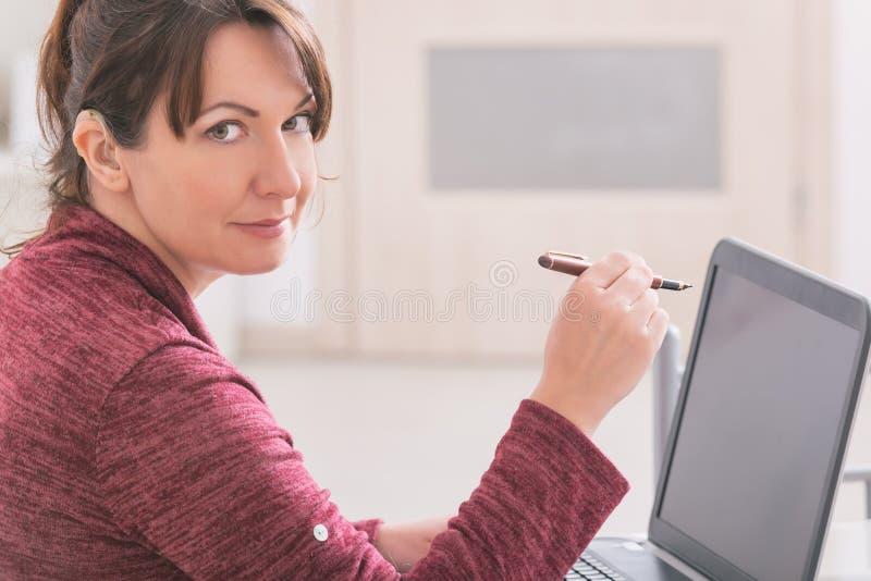 Döv kvinna som hemma använder bärbara datorn royaltyfri fotografi