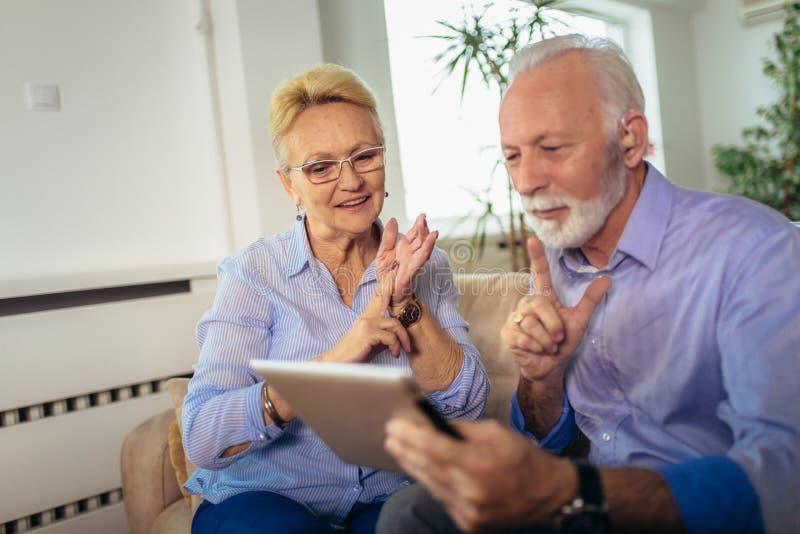 Döva höga par som talar genom att använda teckenspråk på den digitala minnestavlans kam royaltyfri bild