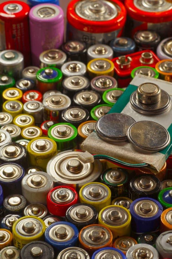 Dúzias dos tipos, dos tamanhos, das cores de baterias usadas e dos acumuladores recycling fotos de stock
