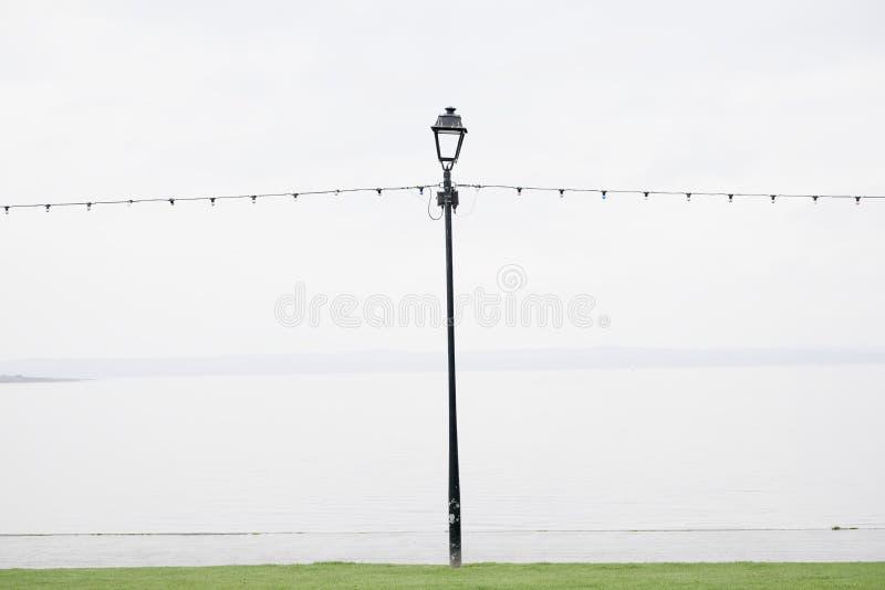 Dû vide de bord de la mer pour mouiller l'été britannique pendant la ligne légère de pluie et le courrier isolés de lampe photos stock