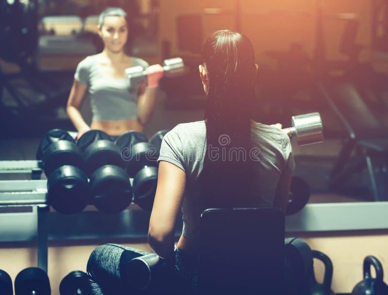 Dünn, hebt Bodybuildermädchen, den schweren Dummkopf an, der vor dem Spiegel bei der Ausbildung in der Turnhalle steht lizenzfreie stockbilder