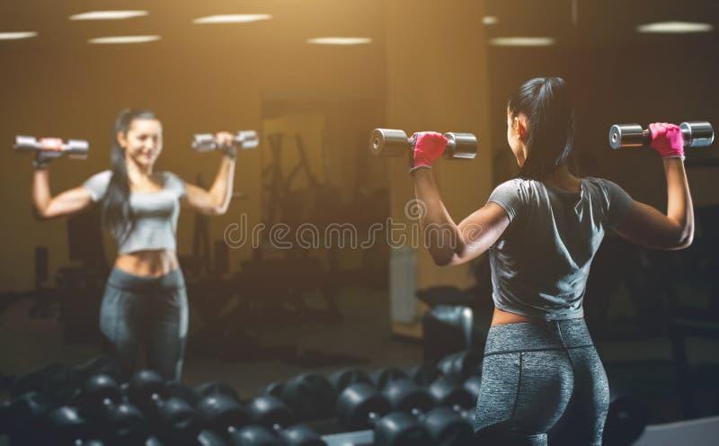 Dünn, hebt Bodybuildermädchen, den schweren Dummkopf an, der vor dem Spiegel bei der Ausbildung in der Turnhalle steht lizenzfreies stockbild