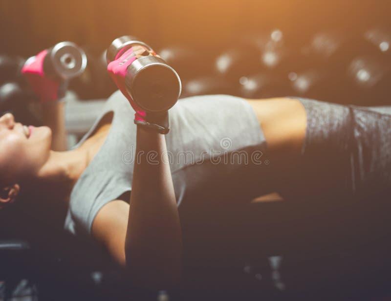 Dünn, hebt Bodybuildermädchen, den schweren Dummkopf an, der vor dem Spiegel bei der Ausbildung in der Turnhalle steht lizenzfreie stockfotografie