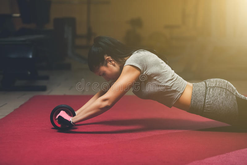 Dünn, tut Bodybuildermädchen, die Übungen mit Rolle für eindrücken die Turnhalle stockbilder