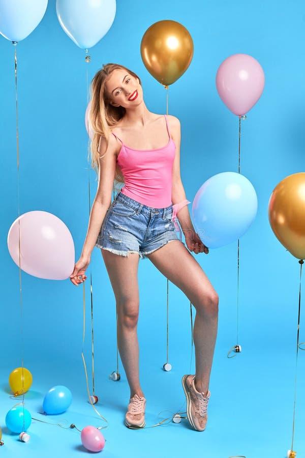 Dünne attraktive lächelnde Blondine, die ihren Geburtstag feiern stockbild