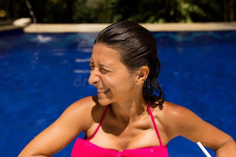 dünne brunette junge Frau, die mit frischer Kokosnuss im Pool mit blauem Kristallwasser aufwirft Königlicher tropischer Erholungs lizenzfreie stockbilder