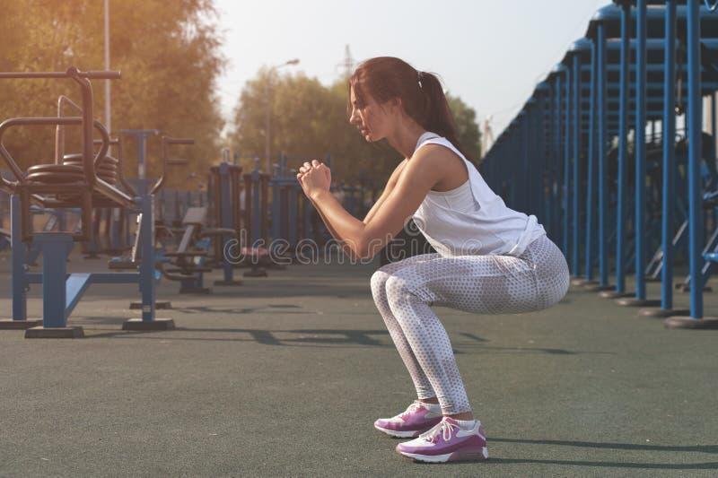 Dünne Brunettefrau, die Turnhalle in der im Freien trainiert stockfoto