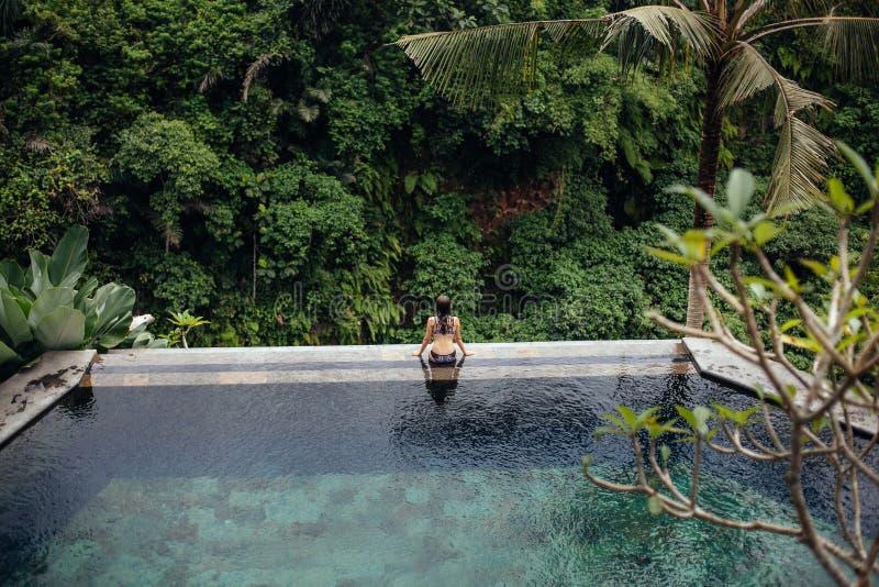 Dünne Brunettefrau im Badeanzug, der auf Randunendlichkeitspool im Dschungel sich entspannt Palmen herum und Kristalltrinkwasser stockfotos