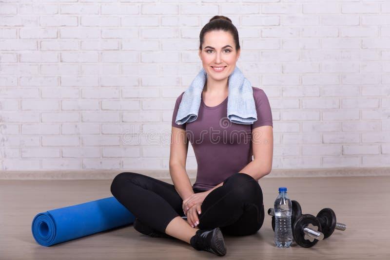 Dünne Frau, die auf dem Boden sitzt, nachdem zu Hause trainieren lizenzfreies stockfoto