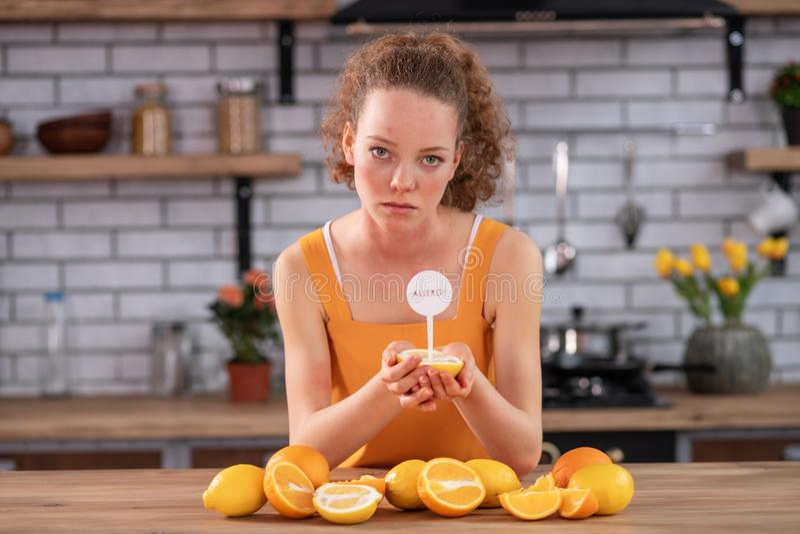 Dünne Frau, die auf Küchentisch sich lehnt und halb von der Zitrone trägt lizenzfreie stockbilder
