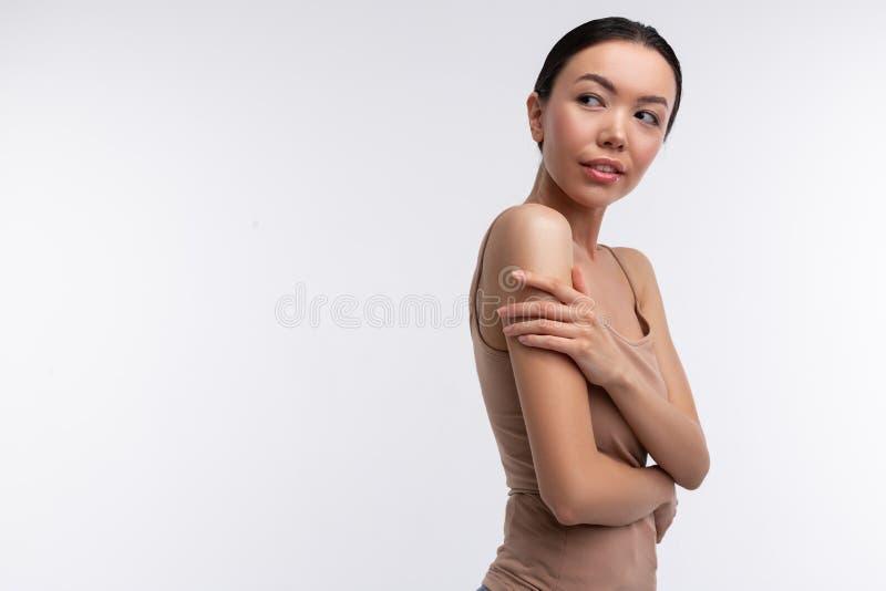 D?nne Frau, die beige Unterhemdstellung nahe Hintergrund tr?gt lizenzfreie stockfotos