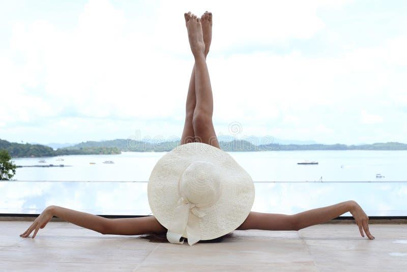 Dünne Frau legen sich hin und heben ihre Beine in der Luft mit großem Hut an stockfotos