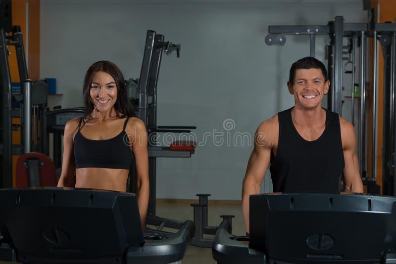 Dünne Frau und muskulöser männlicher Trainer in der Sportturnhalle stockfoto