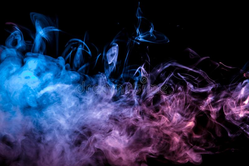 Dünne glatt Windenströme des farbigen Rauches verdunsten gegen einen schwarzen Hintergrund, der mit blauem und rosa Licht wie bel stockbild