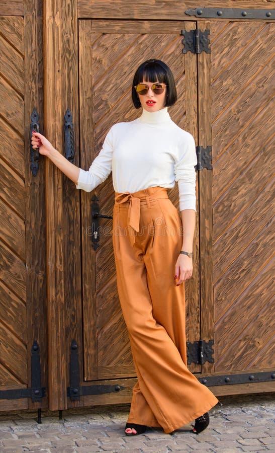 Dünne große Dame der modernen Ausstattung Frauenweg in den losen Hosen Moderner brunette Stand der Frau draußen hölzern lizenzfreies stockfoto