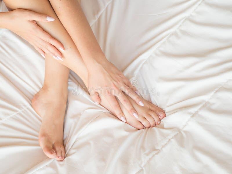 Dünne, perfekte und schöne gekreuzte Frauenbeine auf Bett Geerntetes Bild von auf Bettschönheit erotisch herein liegen lizenzfreie stockfotografie