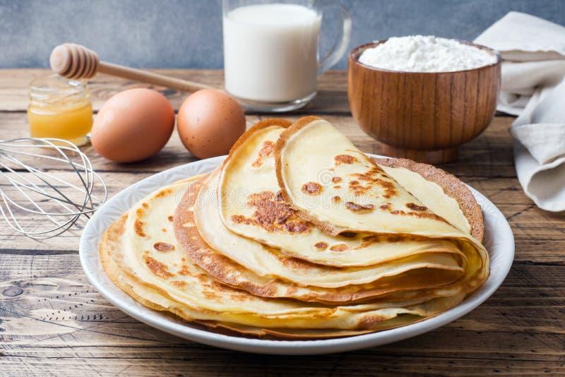 Dünne Pfannkuchen auf einer Platte Hölzerner Hintergrund Bestandteile zum Kochen von Eiern, Milch, Mehl stockbild