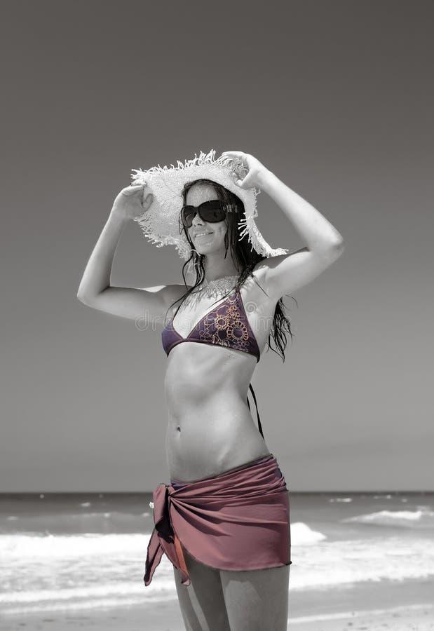 Dünne, reizvolle junge Frau, die Strohhut auf sonnigem Strand justiert stockbild