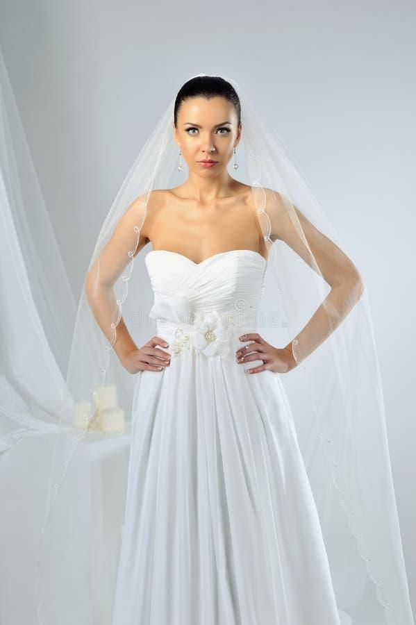 Dünne schöne Frau, die luxuriöses Hochzeitskleid trägt stockfotografie