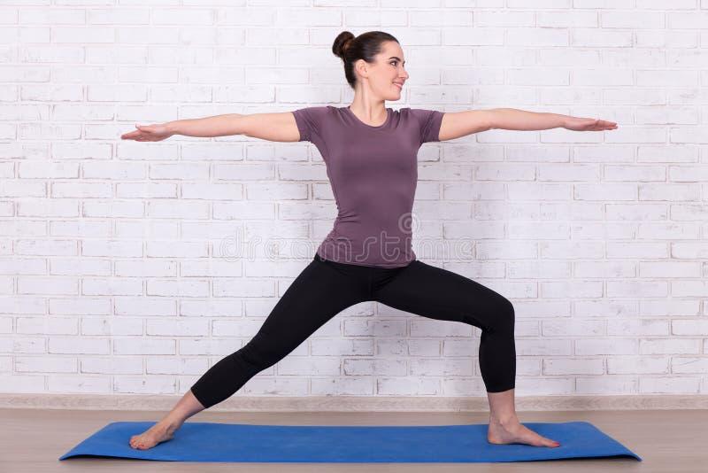 Dünne sportliche Frau über weißer Backsteinmauer stockfoto