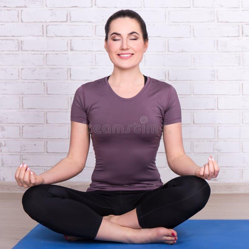 Dünne sportliche Frau, die in der Yogahaltung über weißer Backsteinmauer sitzt lizenzfreie stockfotografie