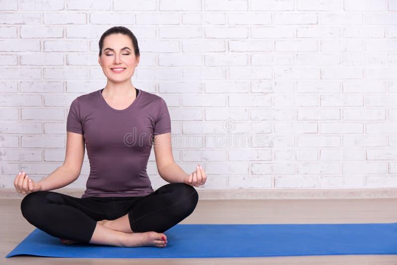 Dünne sportliche Frau, die in der Yogahaltung auf Matte über weißem Ziegelstein w sitzt stockbilder