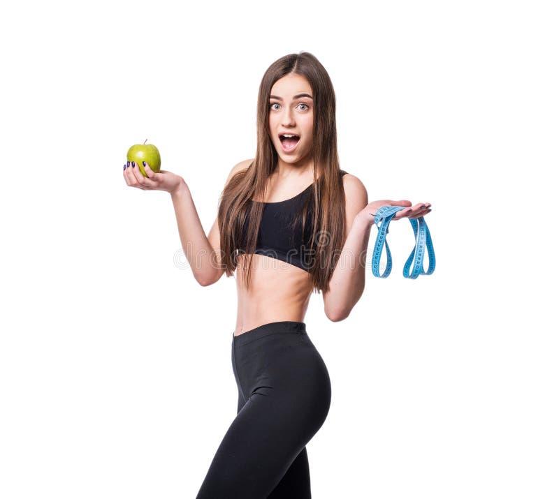 Dünne und gesunde junge Frau, die Maßband halten und Apfel lokalisiert auf weißem Hintergrund Gewichtsverlust und Diätkonzept stockfotografie