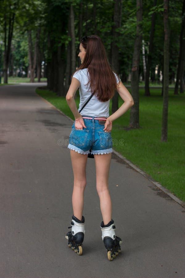 Dünner Brunette jugendlich in den Denimkurzen hosen, die in den Park, rollerblading reiten lizenzfreie stockbilder