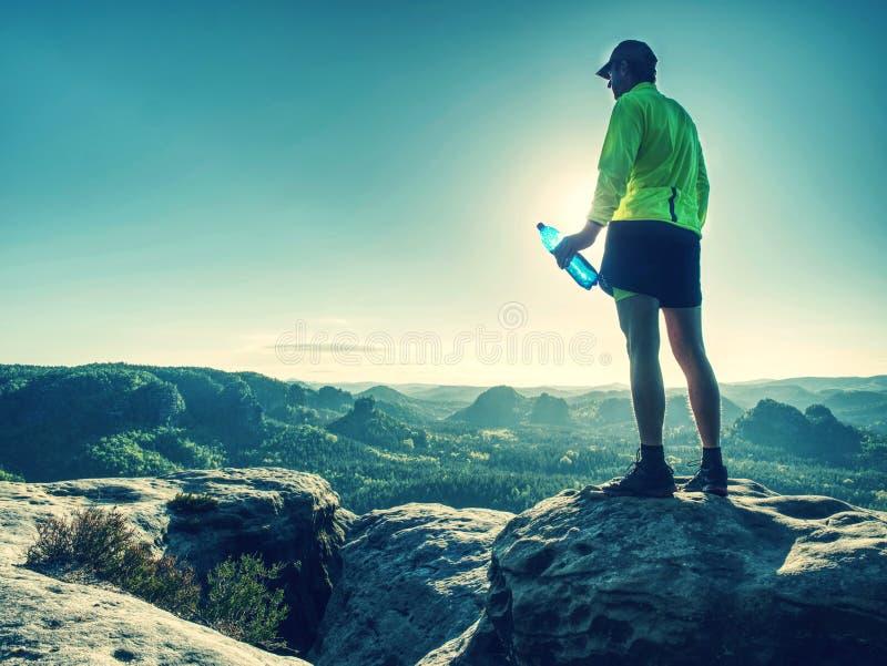 Dünner Mann im gelben Trikot, in den schwarzen kurzen Hosen und in den Laufschuhen laufen gelassen lizenzfreie stockfotografie