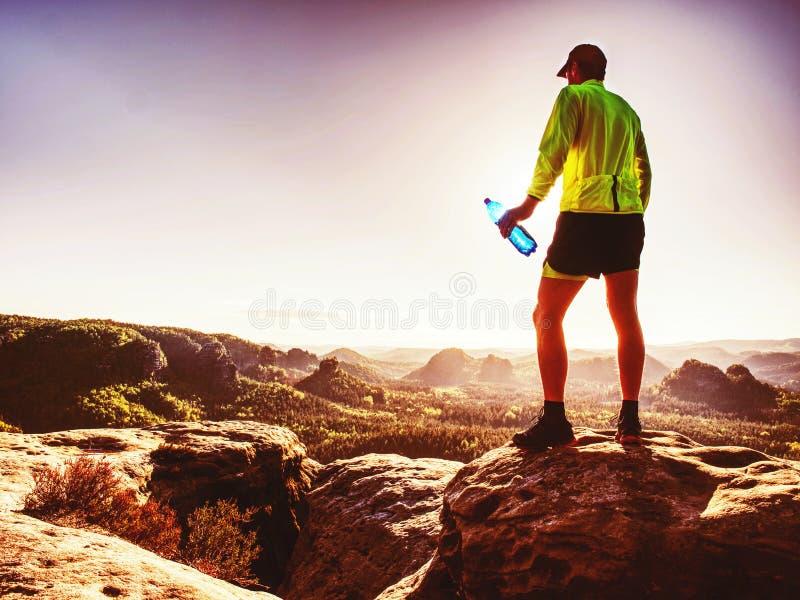 Dünner Mann im gelben Trikot, in den schwarzen kurzen Hosen und in den Laufschuhen laufen gelassen lizenzfreie stockfotos