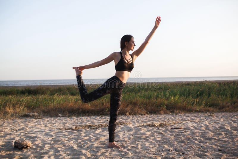 Dünnes brunette junge Frauen-übendes Yoga am Sandstrand Kopieren Sie Platz Gesunder Artsport Virabhadrasana lizenzfreie stockbilder