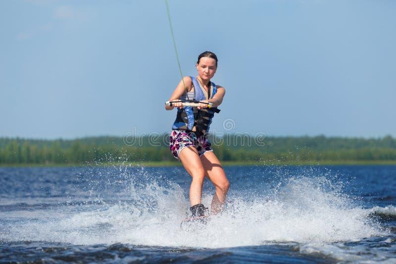 Dünnes Frauenreiten-wakeboard auf Welle des Bootes stockbild