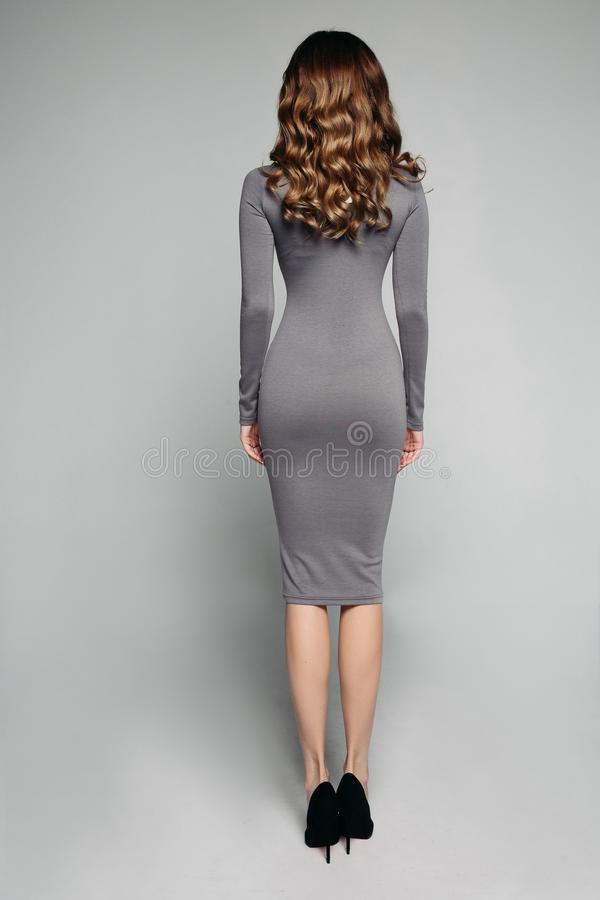 Dünnes großartiges Modell im dünnen grauen Kleid und in den hohen Absätzen stockfotos