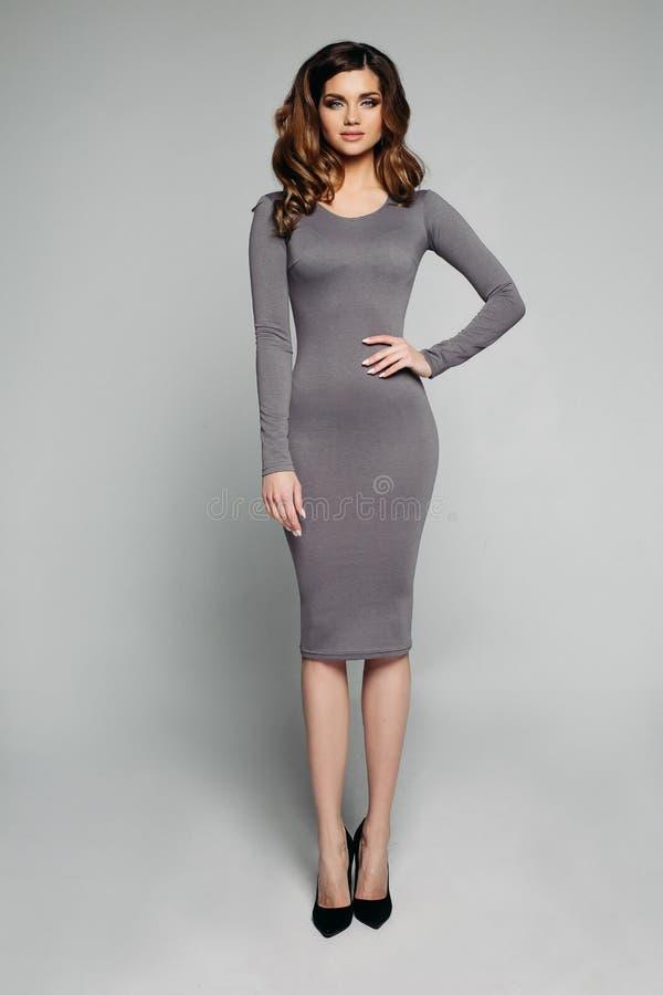 Dünnes großartiges Modell im dünnen grauen Kleid und in den hohen Absätzen lizenzfreie stockfotografie