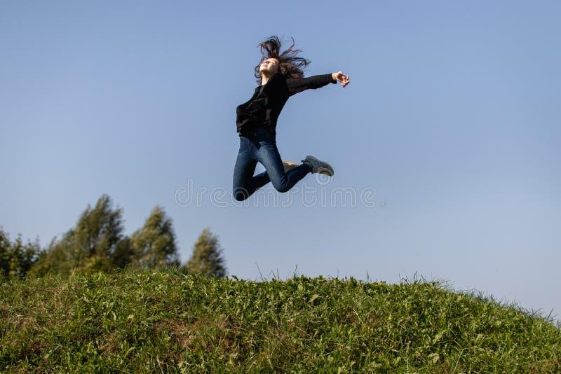 Dünnes jugendlich Mädchen, das hoch über grünes Gras gegen den Himmel springt lizenzfreies stockbild