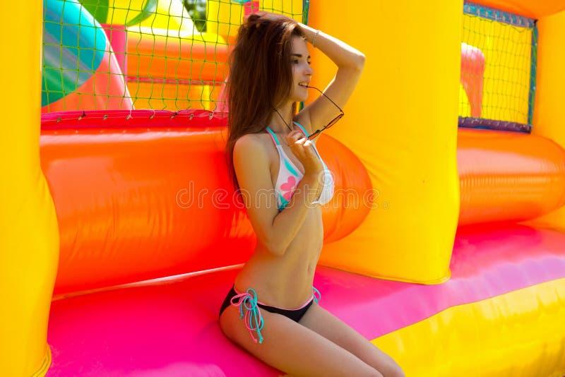 Dünnes junges Brunettemädchen im Badeanzug sitzt auf Mehrfarbenballone draußen lizenzfreie stockbilder