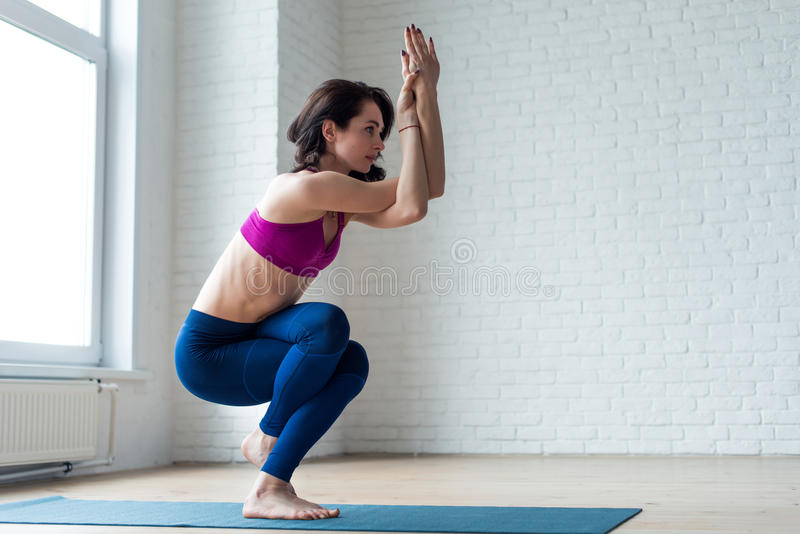 Dünnes Mädchen im Activewear, der Yogaübung Garudasana oder Eagle-Haltung mit bloßen Füßen auf Matte im Sportverein tut lizenzfreie stockfotos