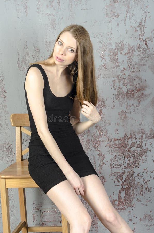 d nnes sch nes rothaariges m dchen in einem schwarzen minikleid mit einem stuhl stockbild bild. Black Bedroom Furniture Sets. Home Design Ideas
