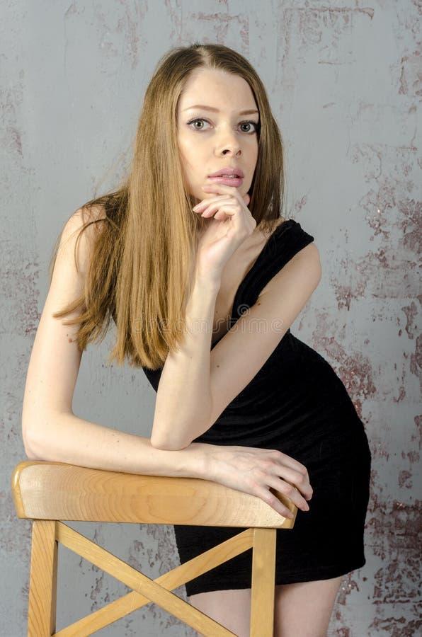 Dünnes schönes rothaariges Mädchen in einem schwarzen Minikleid mit einem Stuhl stockbild