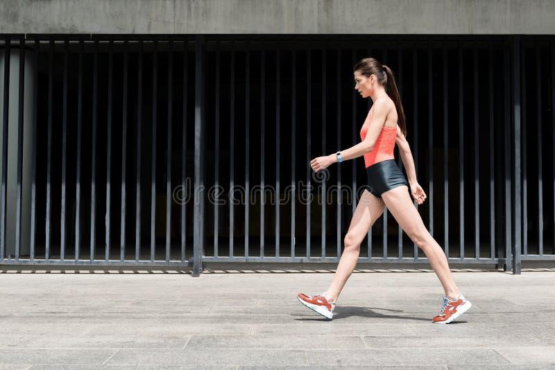 Dünnes sportliches junges Mädchen, das auf Straße geht lizenzfreie stockfotografie