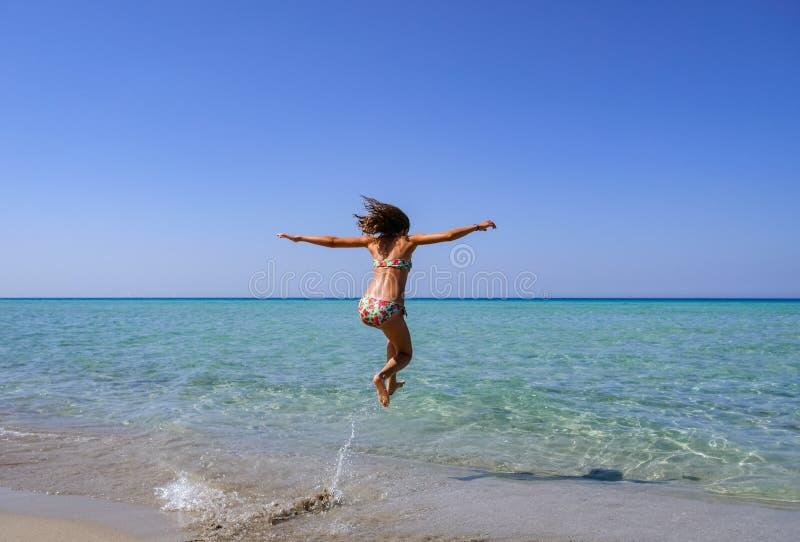 Dünnes und athletisches Mädchen in einem Bikini am Strand, der in das Wasser eines wunderbaren Strandes mit Freude springt lizenzfreie stockfotos