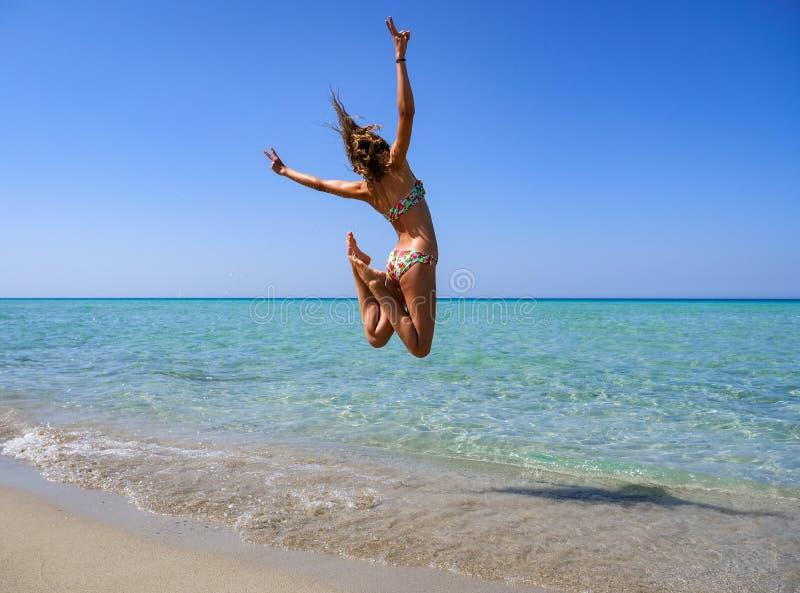 Dünnes und athletisches Mädchen in einem Bikini am Strand, der in die Luft mit Freude springt lizenzfreie stockfotografie