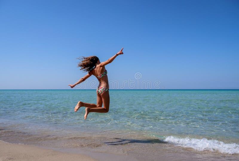 Dünnes und athletisches Mädchen in einem Bikini am Strand, der in die Luft mit Freude springt lizenzfreies stockbild