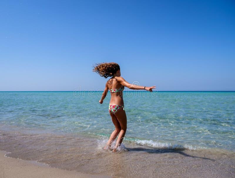 Dünnes und athletisches Mädchen in einem bunten Bikini, der Spaß auf einem wunderbaren Strand mit haarscharfem Wasser hat lizenzfreie stockbilder