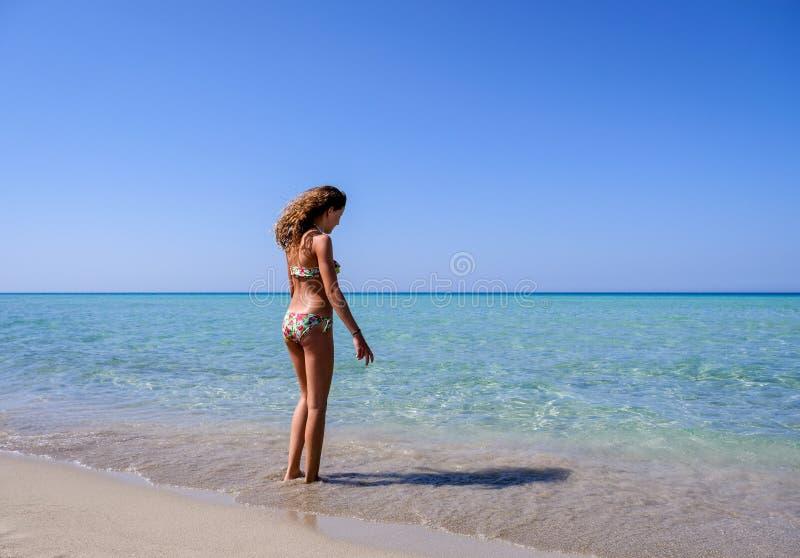 Dünnes und hübsches Mädchen in einer bunten Bikinistellung auf einem wunderbaren Strand mit haarscharfem Wasser lizenzfreies stockbild