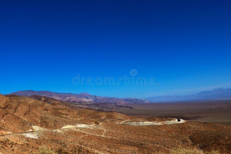 Dürftige Vegetation und eine Schotterwegwicklung in Richtung zum Horizont im bolivianischen altiplano vor dem hintergrund der Ber lizenzfreie stockbilder