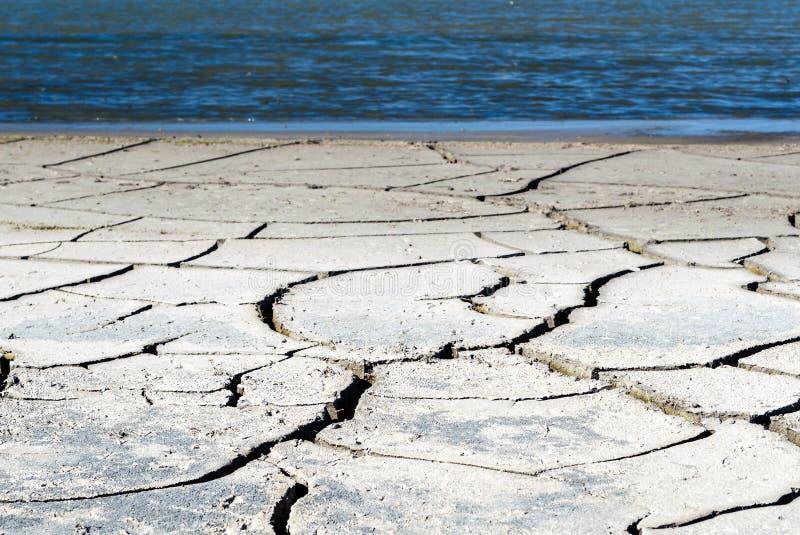 Dürrenufer eines Reservoirs mit großen Sprüngen im Boden lizenzfreie stockbilder